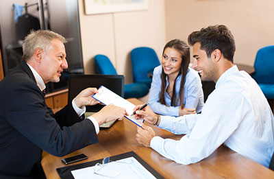 Couple signing a document with another person