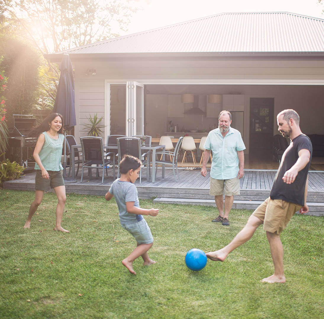 Family kicking a soccer ball in their backyard